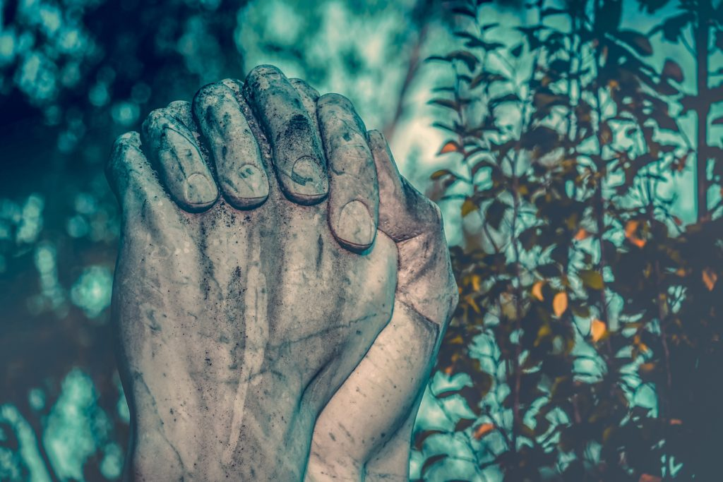 Image of hands praying from monument