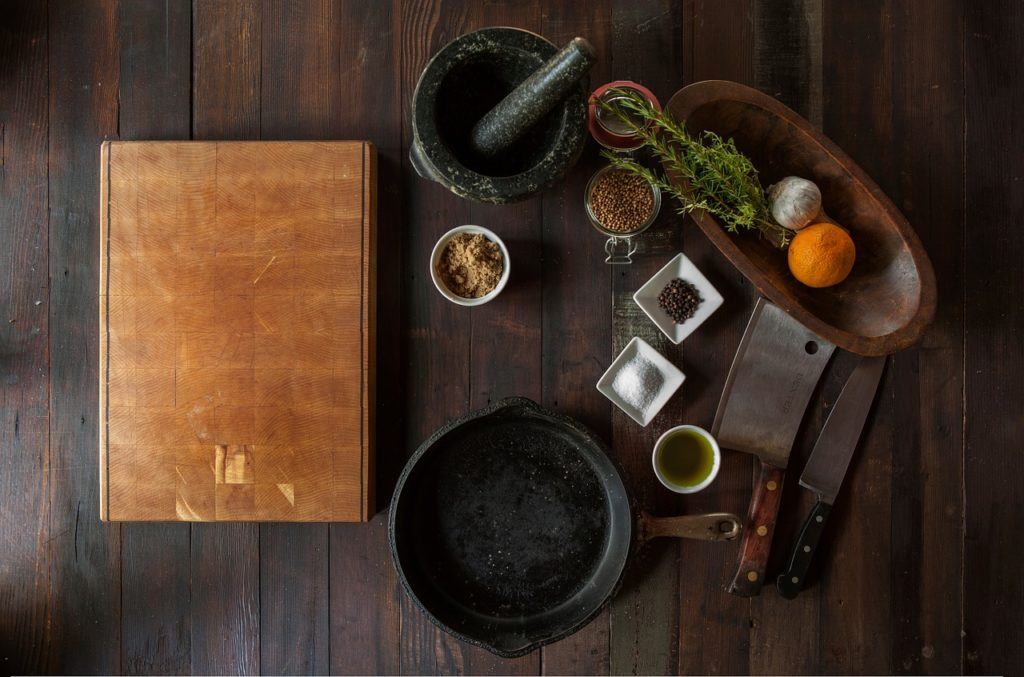 image of cooking ingredients, pot, and grinder on brown wood table