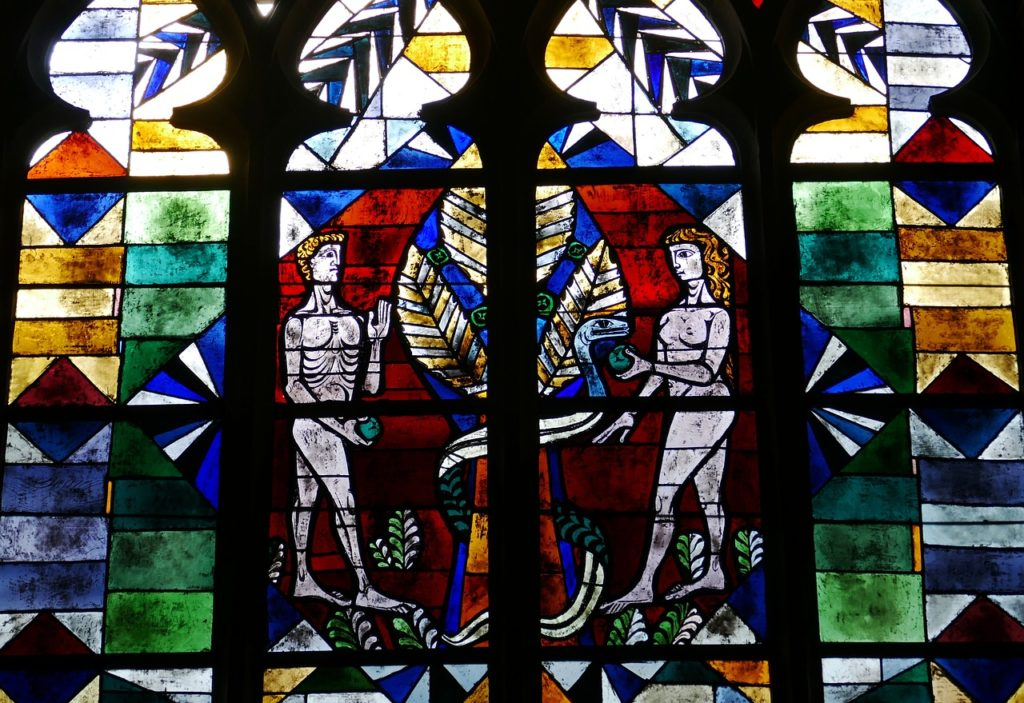 image of dark blue and black stained glass window depicting adam and eve in the garden of eden