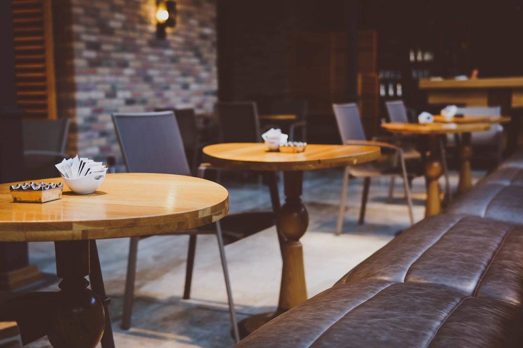 image of brown leather couches and wooden tables in coffee shop