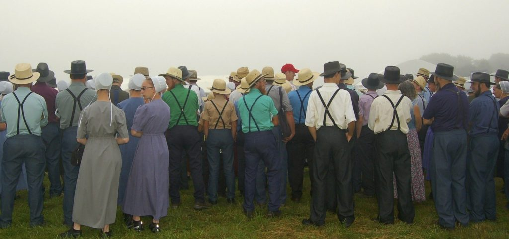 image of people gathered in a field dressed in clothes associated with Amish communities