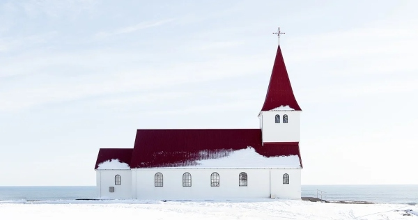 white church with red roof in white snow