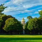 university of notre dame golden dome behind vivid green grass and trees