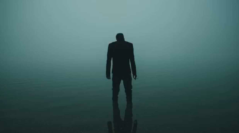 silhouette of a man standing in dark water