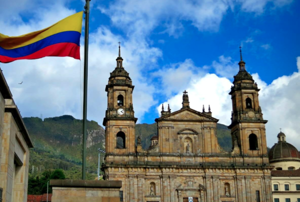 photograph of the Colombian flag flying over Bogota under a blue sky