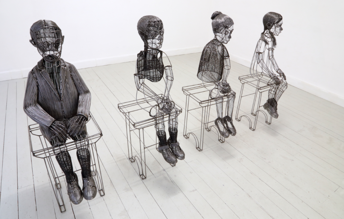 photograph of a Roberto Fanari sculture; four seating human figures made of wire