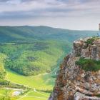 Girl on mountain peak looking over valley